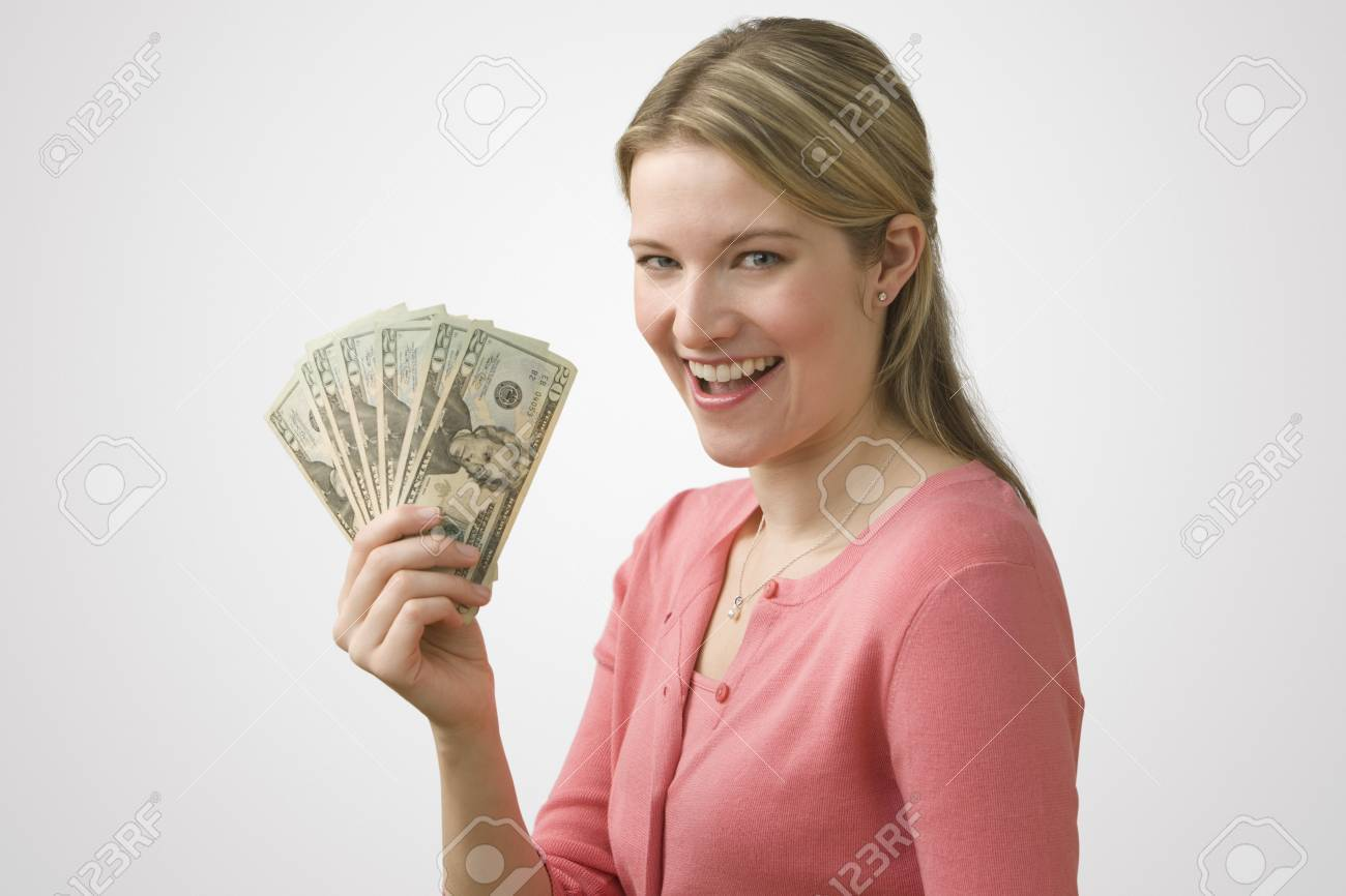 A young woman is holding up cash in a fan and smiling at the camera.  Horizontal shot. Stock Photo - 7467357