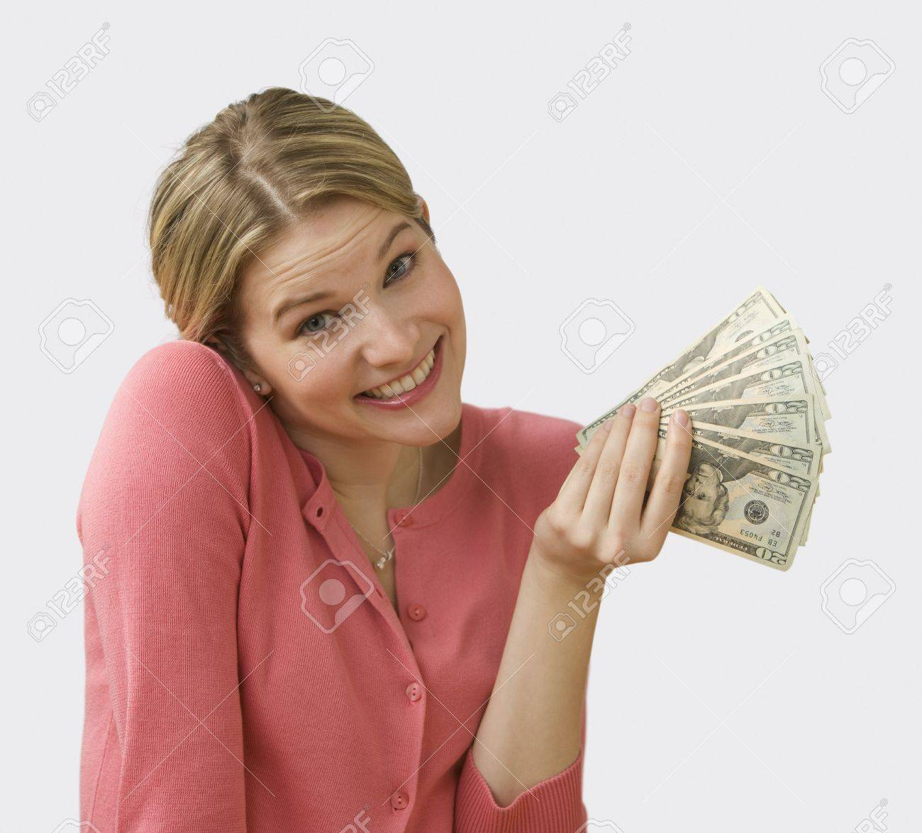 Beautiful young woman fans out cash and shrugs her shoulders.  Square shot. Stock Photo - 7467360
