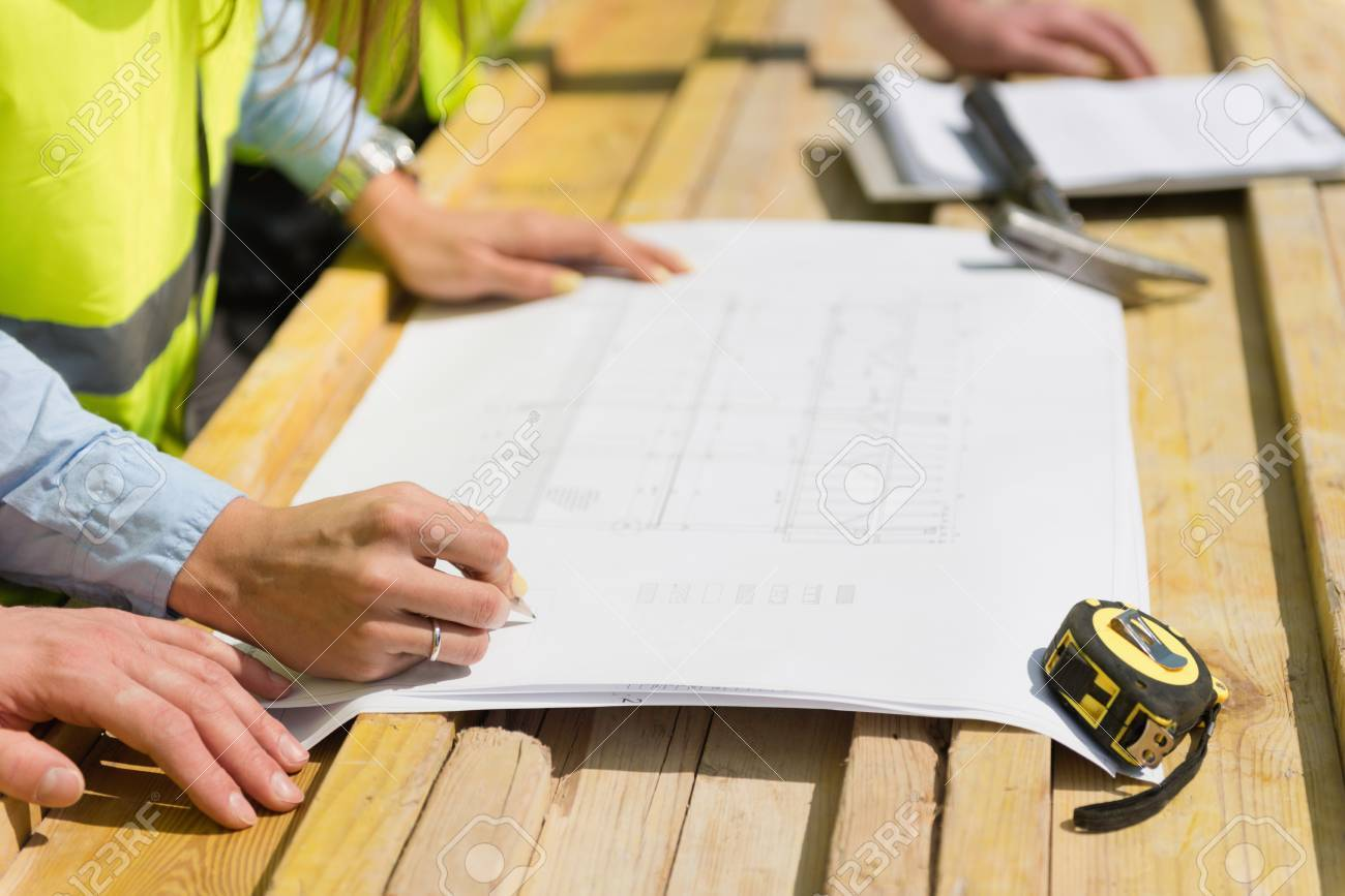 Architect over blueprint on a construction site meeting stock photo architect over blueprint on a construction site meeting stock photo 54129739 malvernweather Images