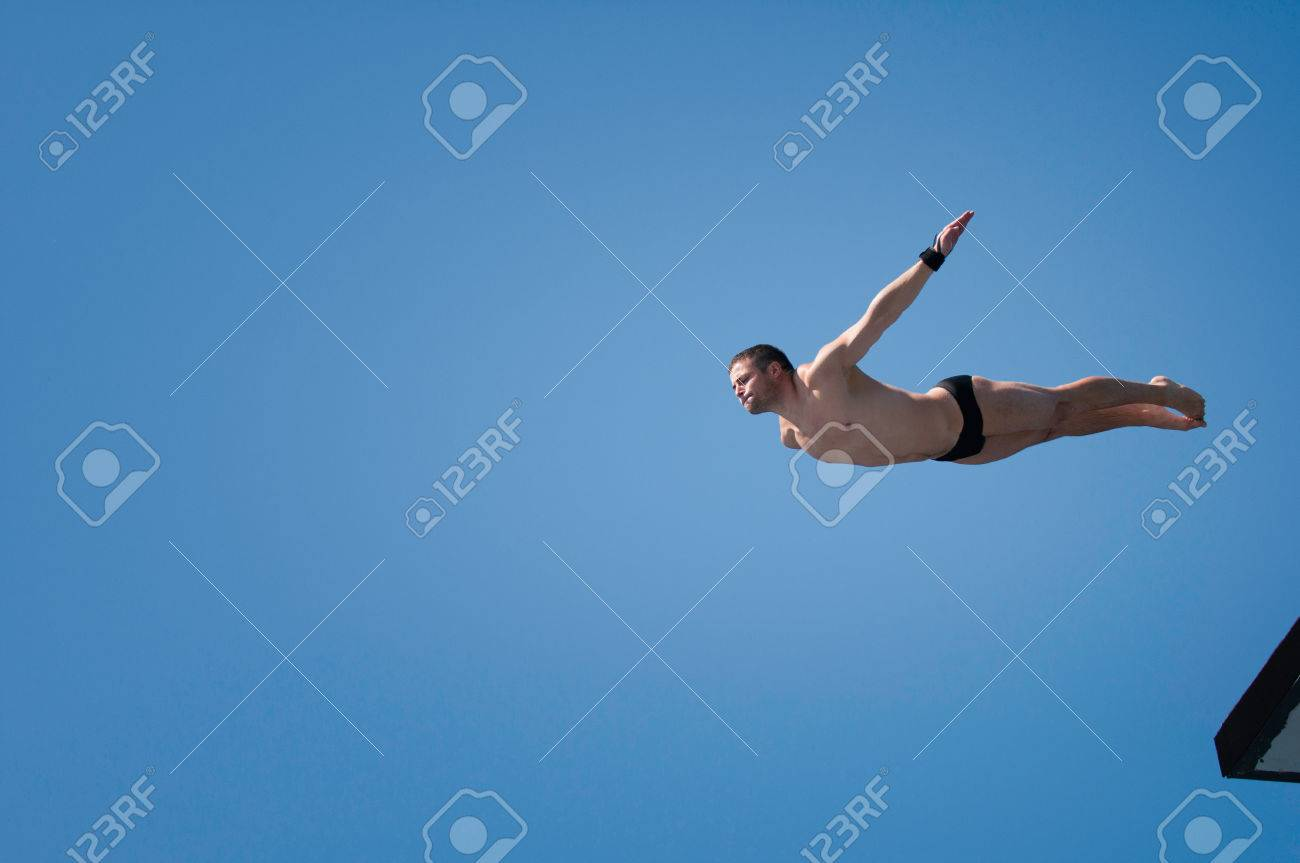 Young man swan diving from 10 meter high platform - 54474617