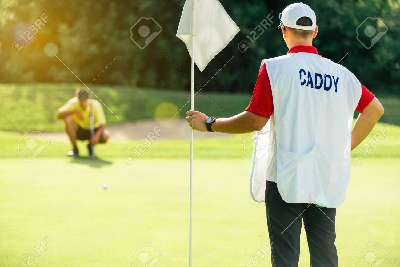 Golf - caddy holding flag, golfer reading green
