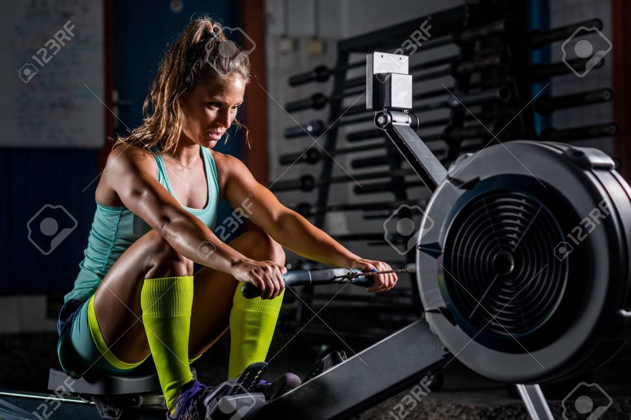 Woman athlete exercising on rowing machine - 83350446