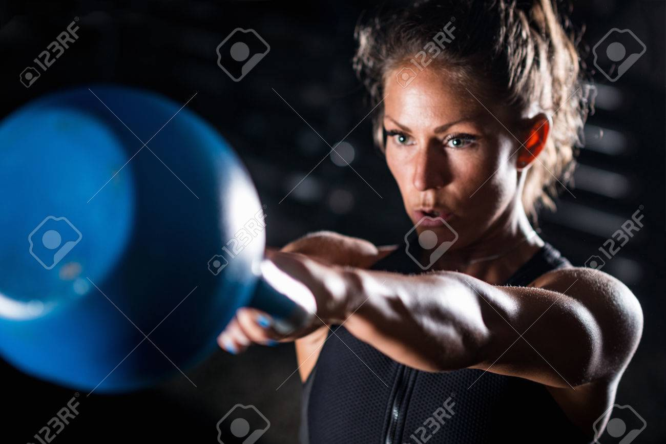 Woman athlete exercising with kettlebell indoors - 83350455