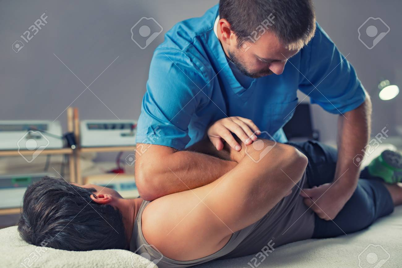 Physiotherapist doing healing treatment on man's back. Therapist wearing blue uniform. Osteopathy. Chiropractic adjustment, patient lying on massage table - 106884169