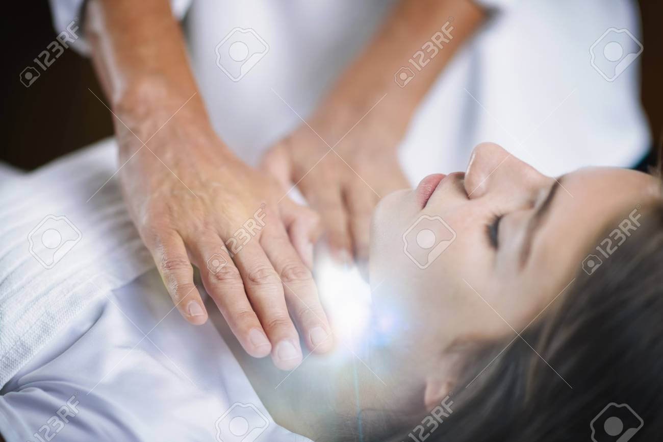 Reiki practitioner standing and healing throat chakra to beautiful