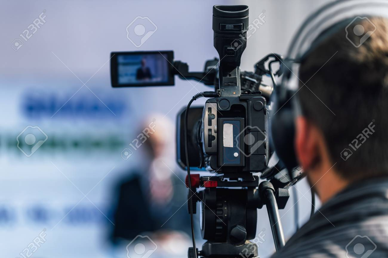 Cameraman wearing headphones and recording male speaker standing on the stage at press conference media event. - 114931725