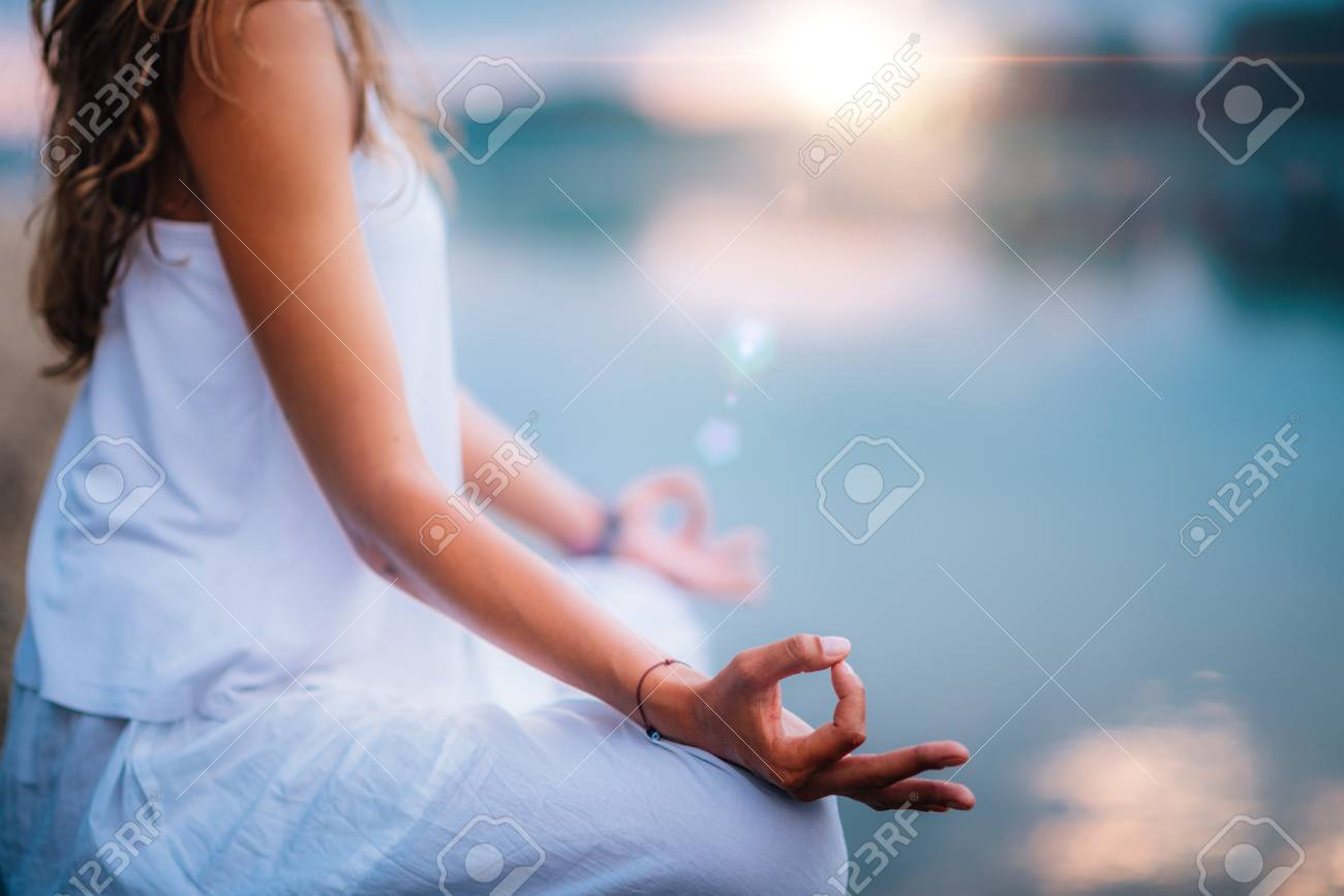 Beautiful young woman doing yoga exercise by the lake. Sitting in lotus position - 115177607