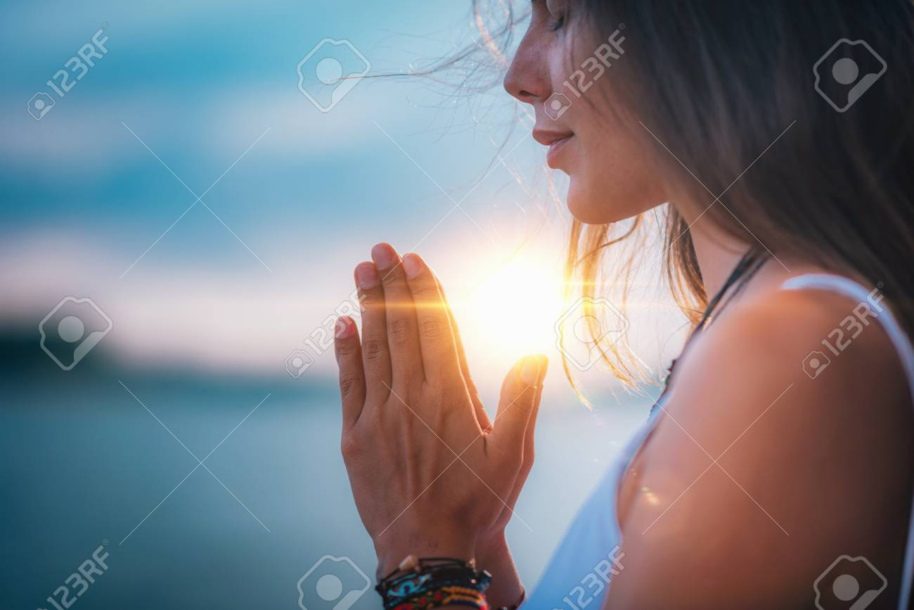 Young woman meditating with her eyes closed, practicing Yoga with hands in prayer position. - 115177780