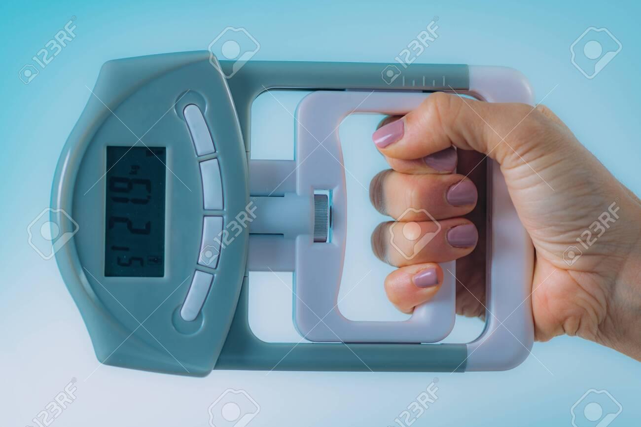 Woman Using Digital Hand Grip Dynamometer - 127711070
