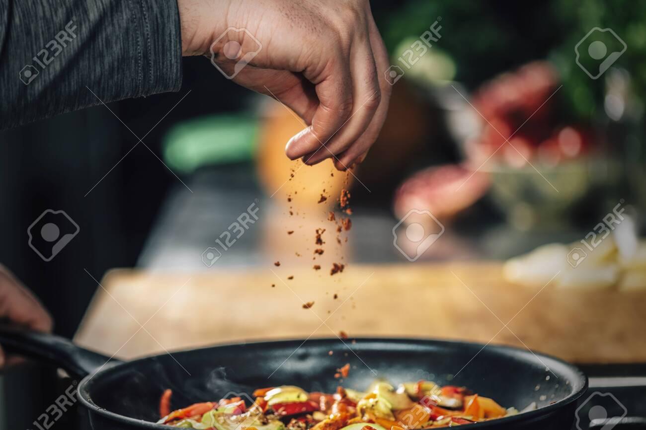 Sprinkling ground red chili pepper paprika over sliced vegetables, motion blur - 141282335