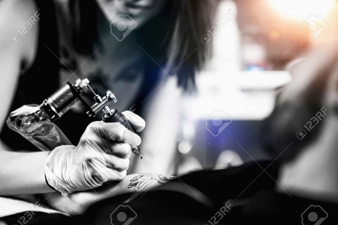 Professional female tattooist working in a tattoo studio - 157382136