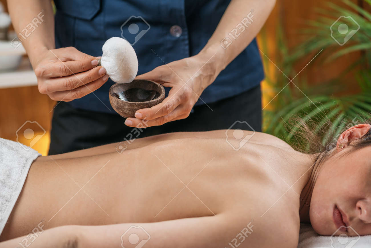 Kizhi or Herbal Bags Ayurveda Massage. Ayurvedic massage practitioner dipping cotton-wrapped herbal bundle into aromatic oil. - 169297520