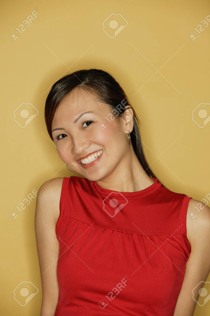 3497360f49a346 Stock Photo - Young woman wearing a red top, against a yellow background