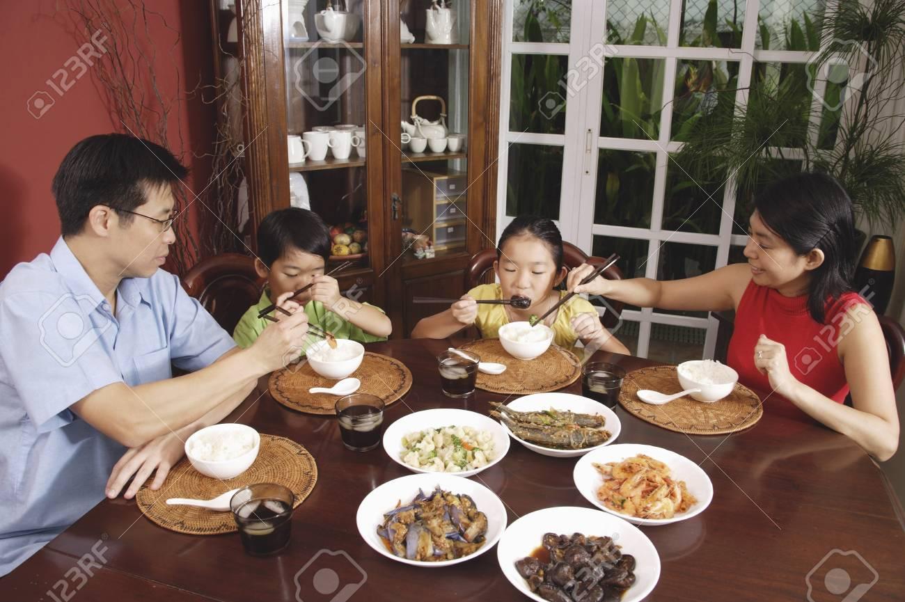 Family of four having dinner at home - 69312166