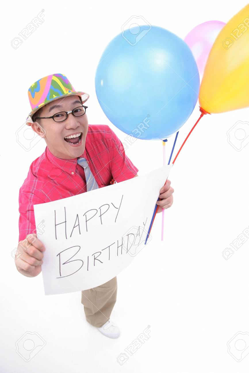 Man With Party Hat Holding Balloons And A Birthday Greeting Sign Stock Photo