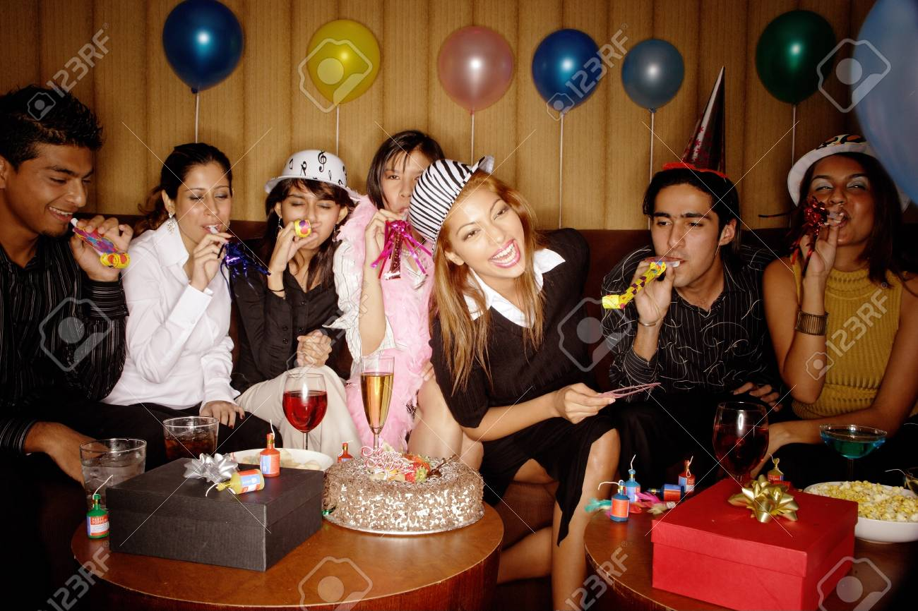 Young Adults Celebrating Birthday Wearing Party Hats Stock Photo