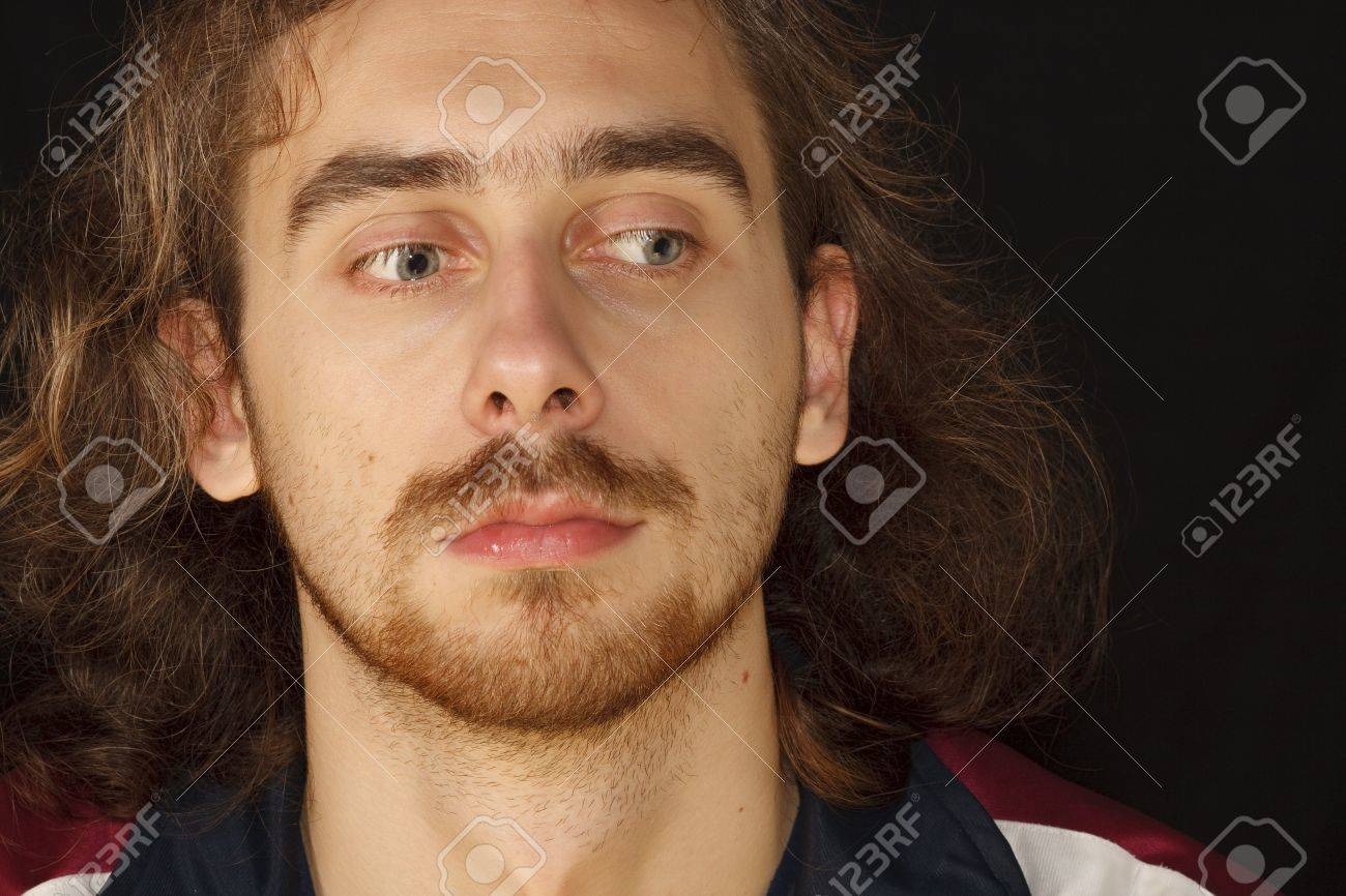 Scared face of young adult man with untidy curly hair, black background Stock Photo - 3988457