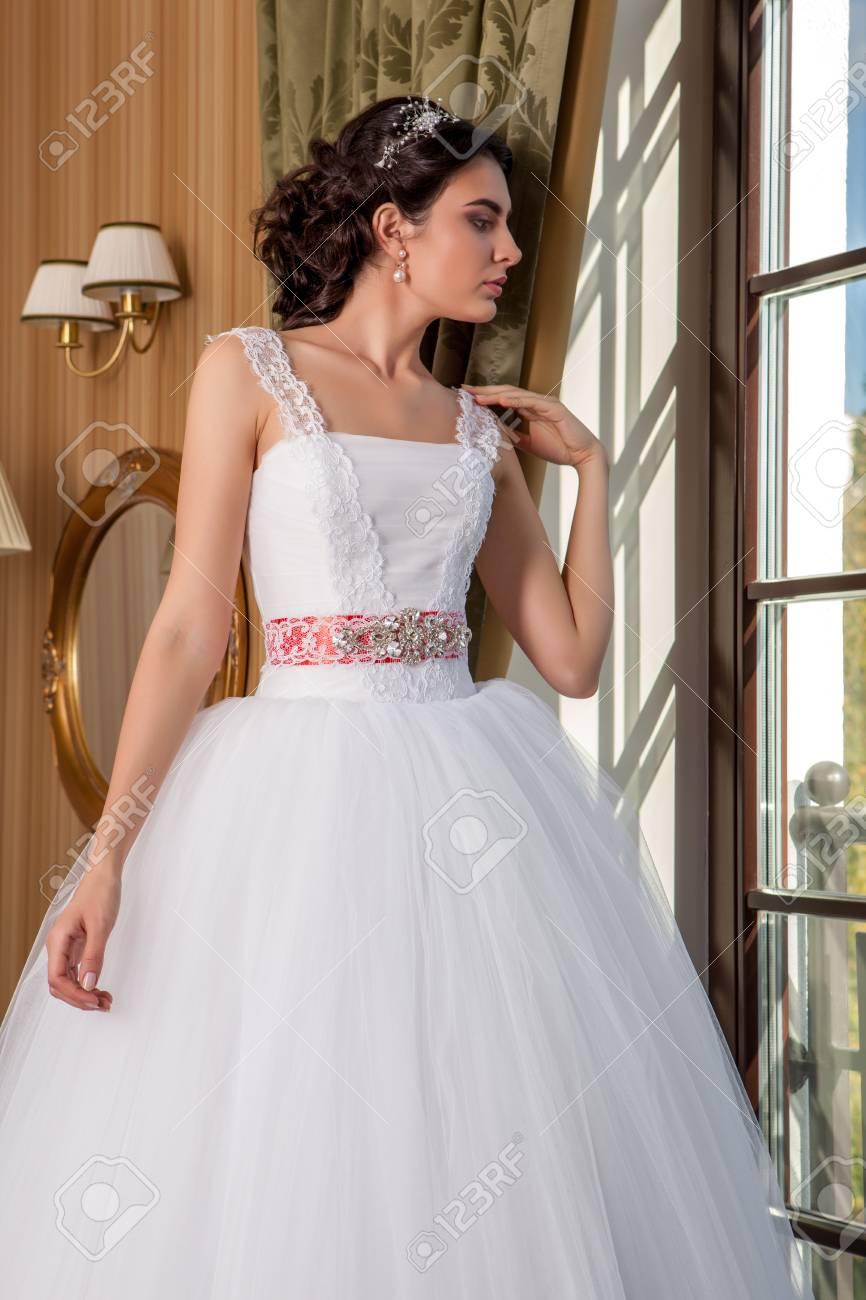 acbaa64c5 Foto de archivo - Vestido de boda. Novia joven que intenta en un vestido de  novia en el salón.