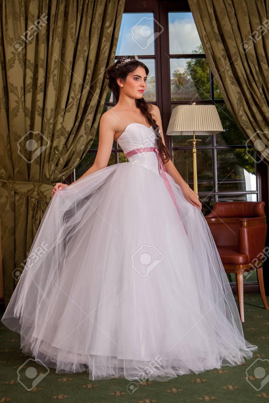 a1d9a776b Foto de archivo - Vestido de novia. Novia joven que intenta en un vestido  de novia en el salón.