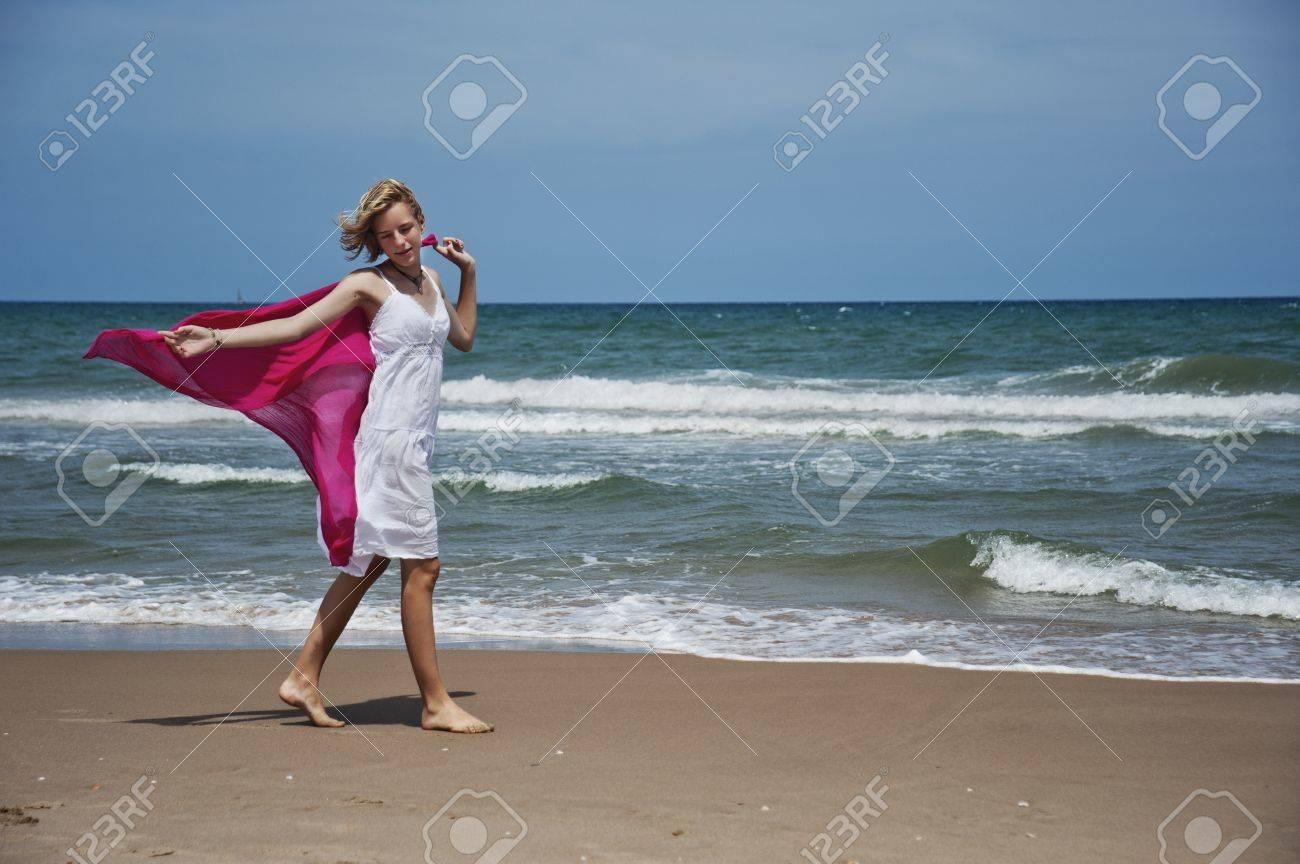 Chica rubia paseando por la orilla con la bufanda del viento Foto de archivo - 14755148