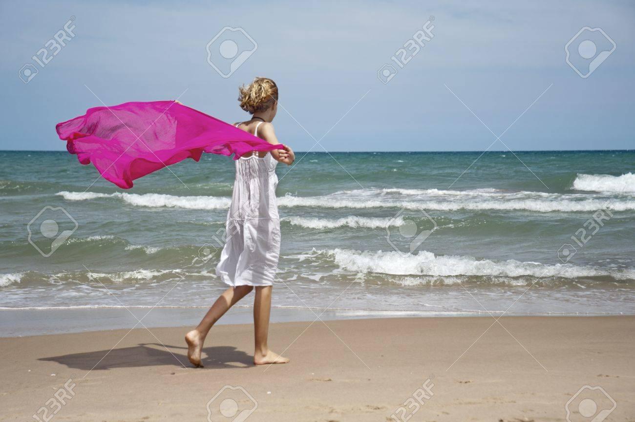 Chica rubia paseando por la orilla con la bufanda del viento Foto de archivo - 14755143