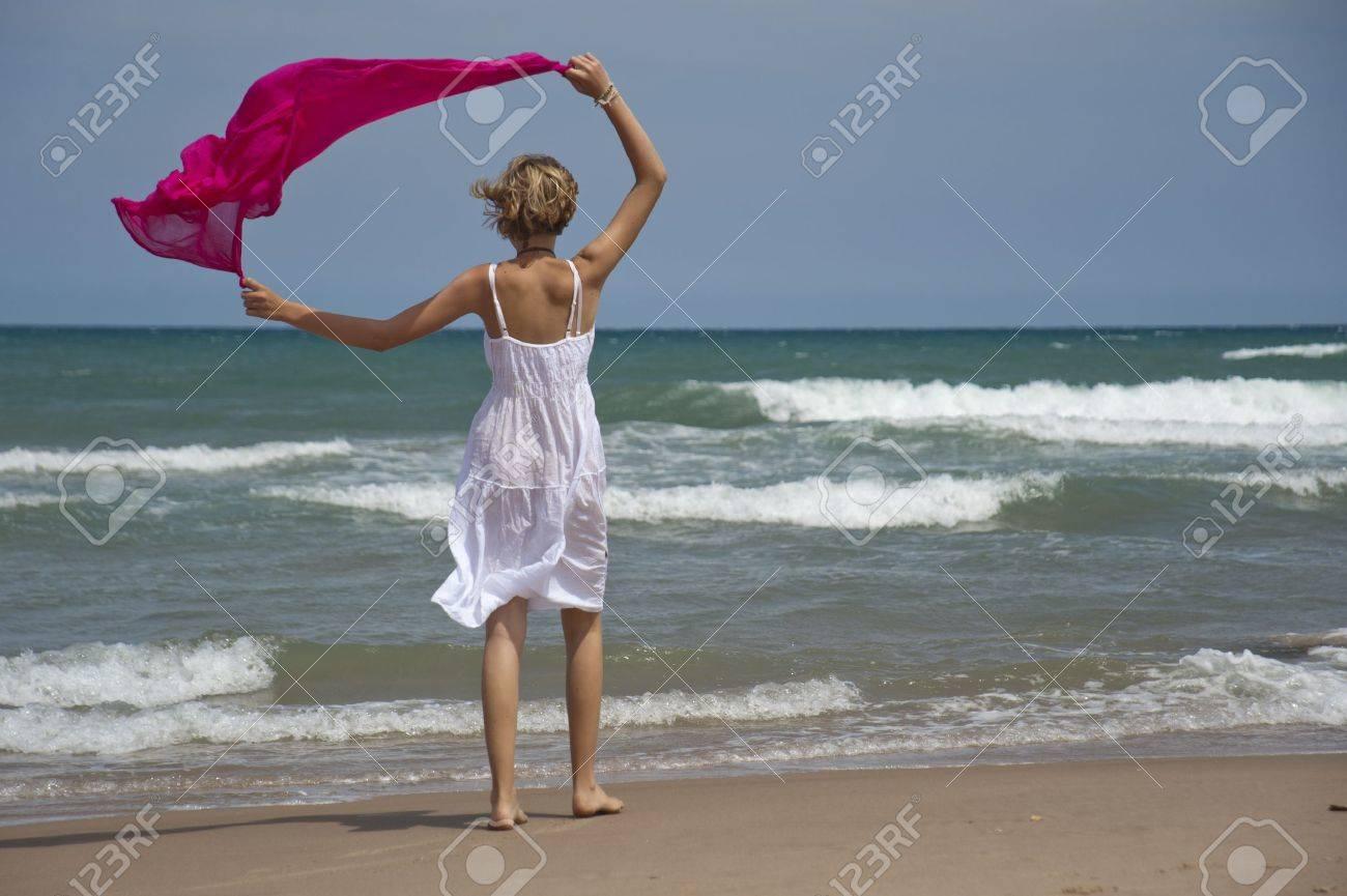 Chica rubia caminando por la orilla con la bufanda del viento Foto de archivo - 14755141