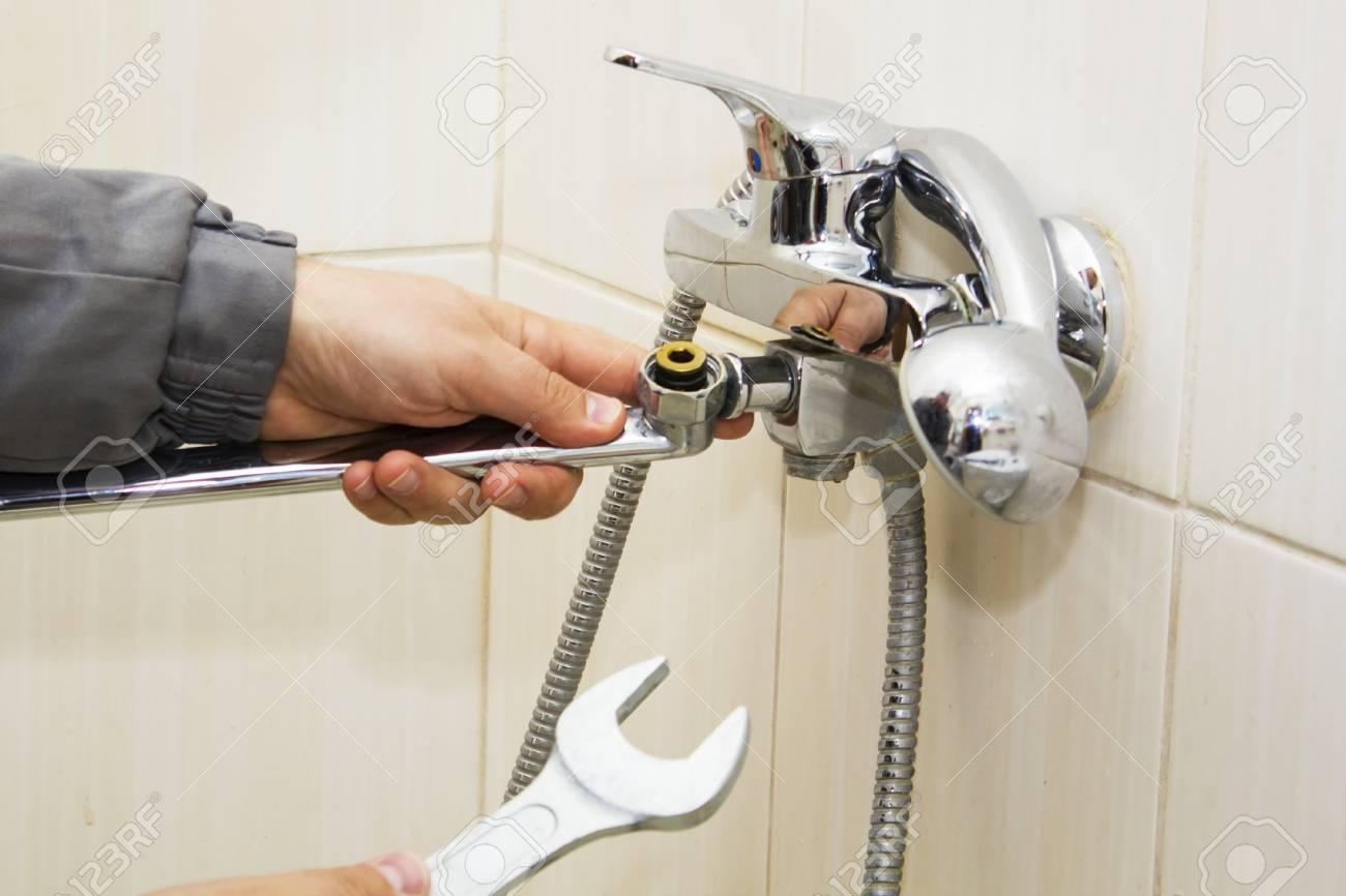 Mains Plombier Fixation Robinet D Eau Avec Une Cle Banque D Images