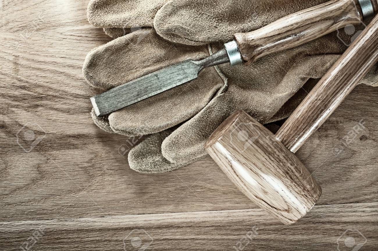 Lump hammer flat chisel protective gloves on wood board. - 105587307