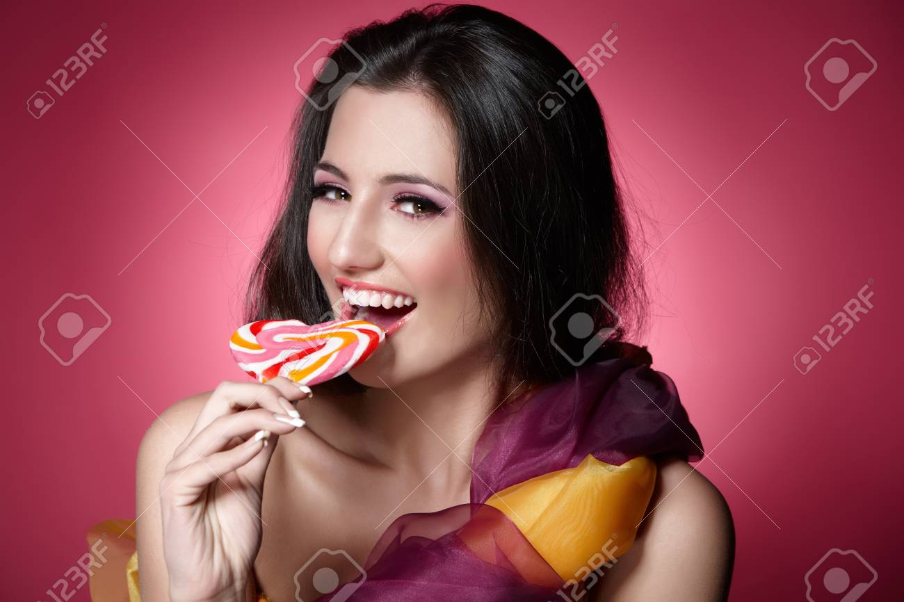 Portrait of a girl holding lollypop over pink background Stock Photo - 9944879