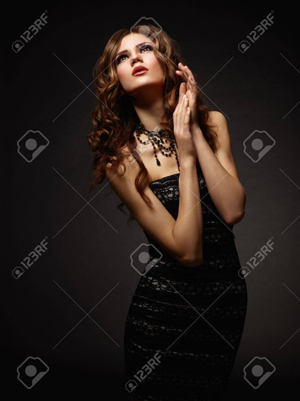 Young attractive woman praying over dark background Stock Photo - 13401605