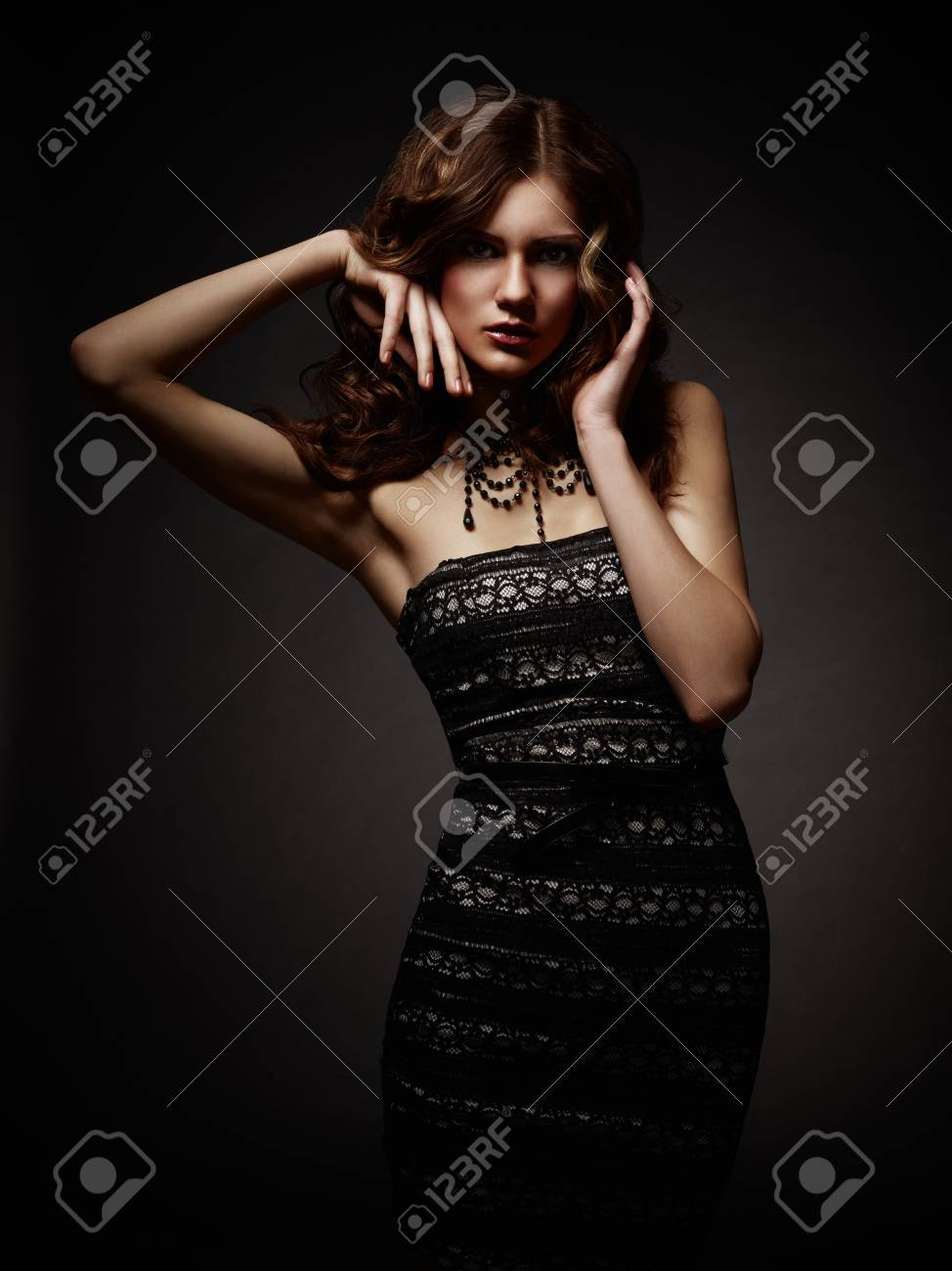 Young attractive woman praying over dark background Stock Photo - 13401611