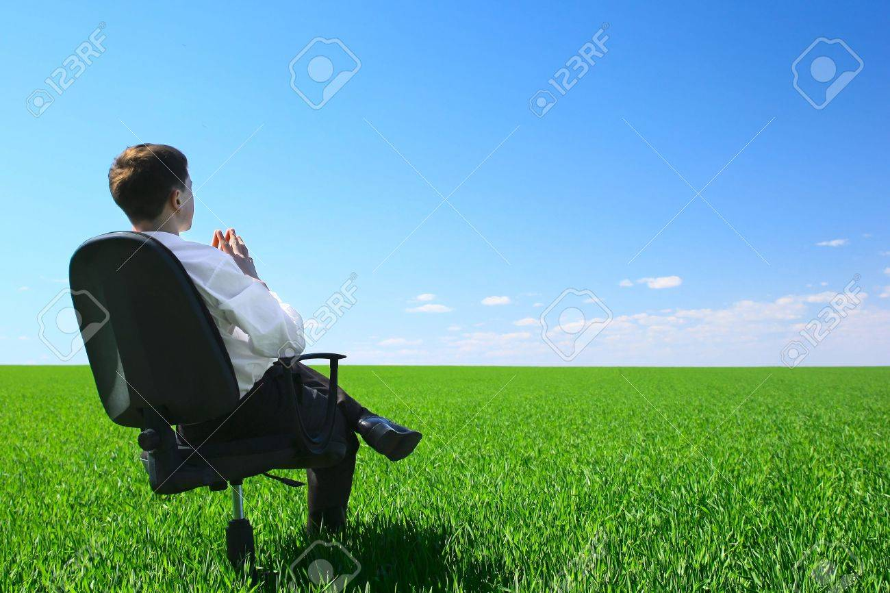 Young man sitting in chair on green meadow over blue clear sky Stock Photo - 7112591
