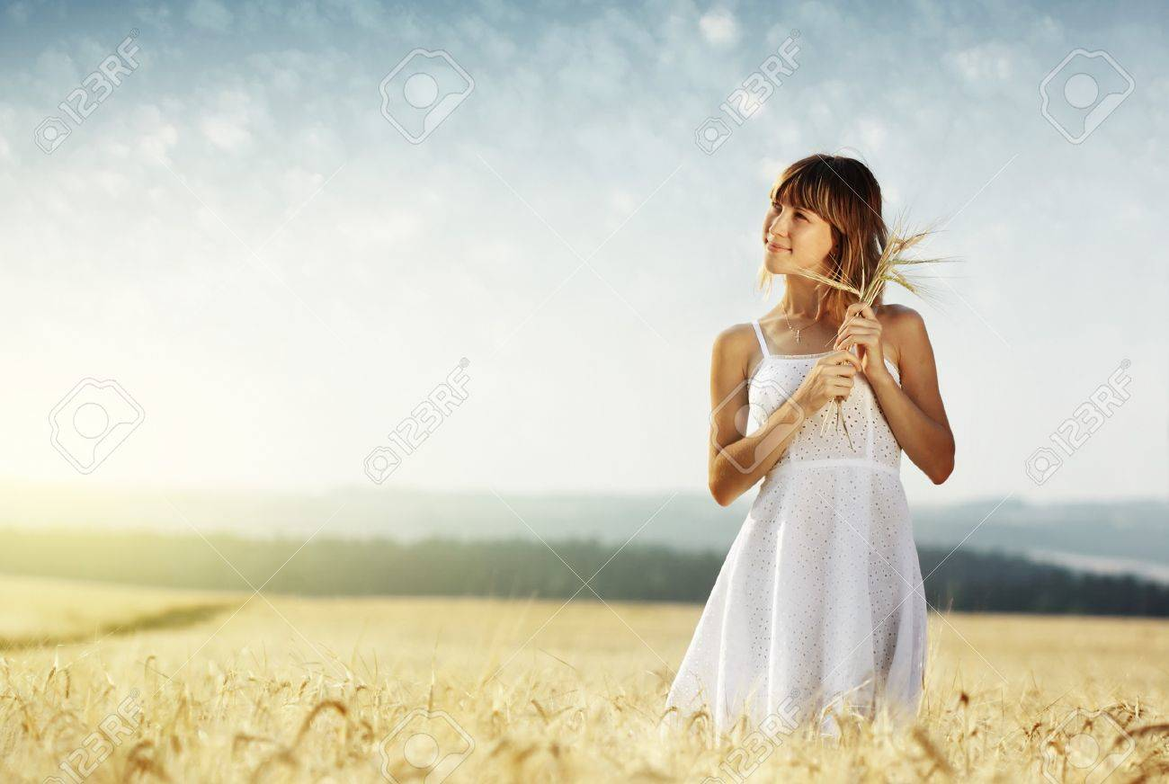Young smiling woman in white dress standing in field Stock Photo - 7600020