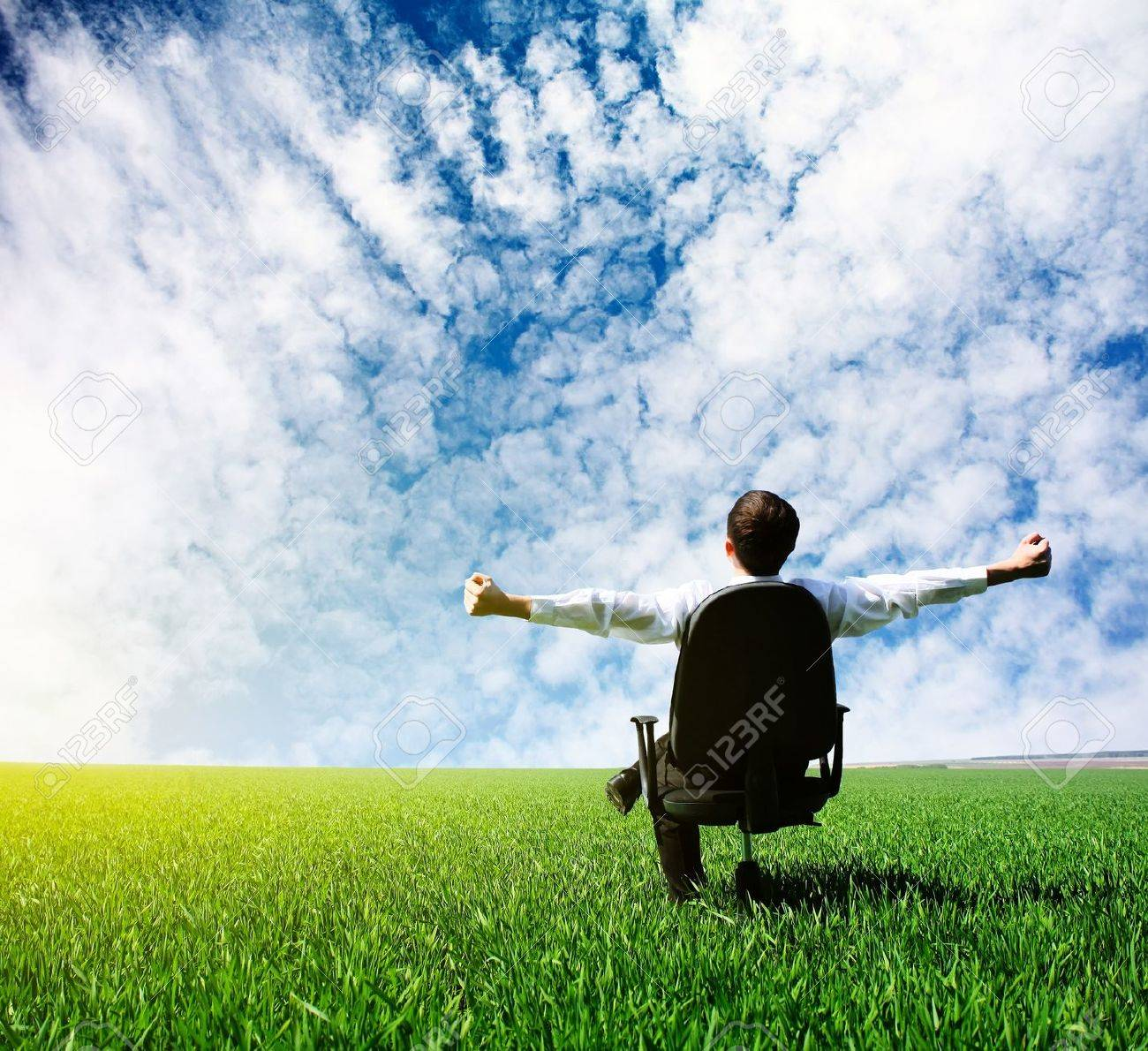 Man with raised hands sitting on chair on green meadow Stock Photo - 7888889