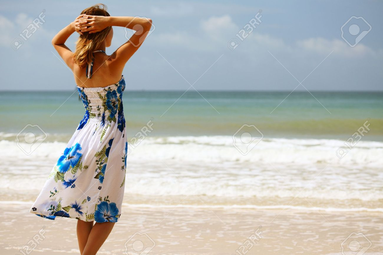 Young woman in dress standing on sand and looking to a sea - 8123508