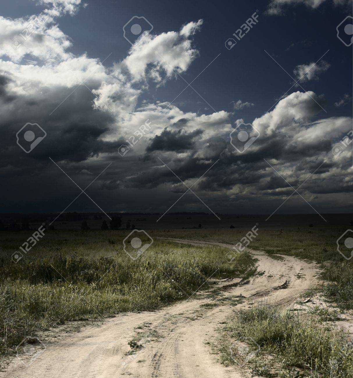 Rural road in field with wild herbs and dark storm clouds Stock Photo - 8323241