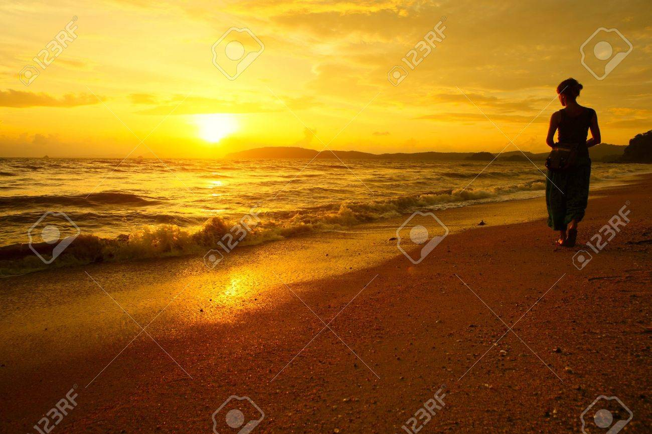 Young woman walking on beach under sunset light Stock Photo - 8333411