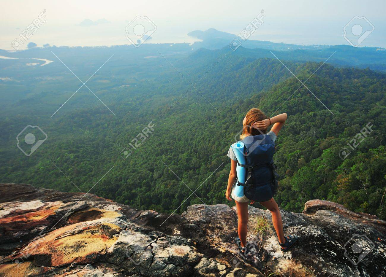 Young woman with backpack standing on cliff's edge and looking to a sky Stock Photo - 9633908