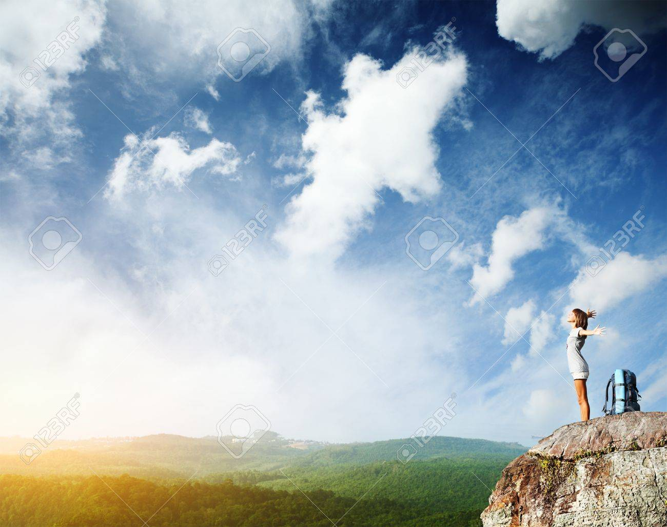 Young woman with backpack standing on cliff's edge with raised hands and looking to a sky Stock Photo - 9633905