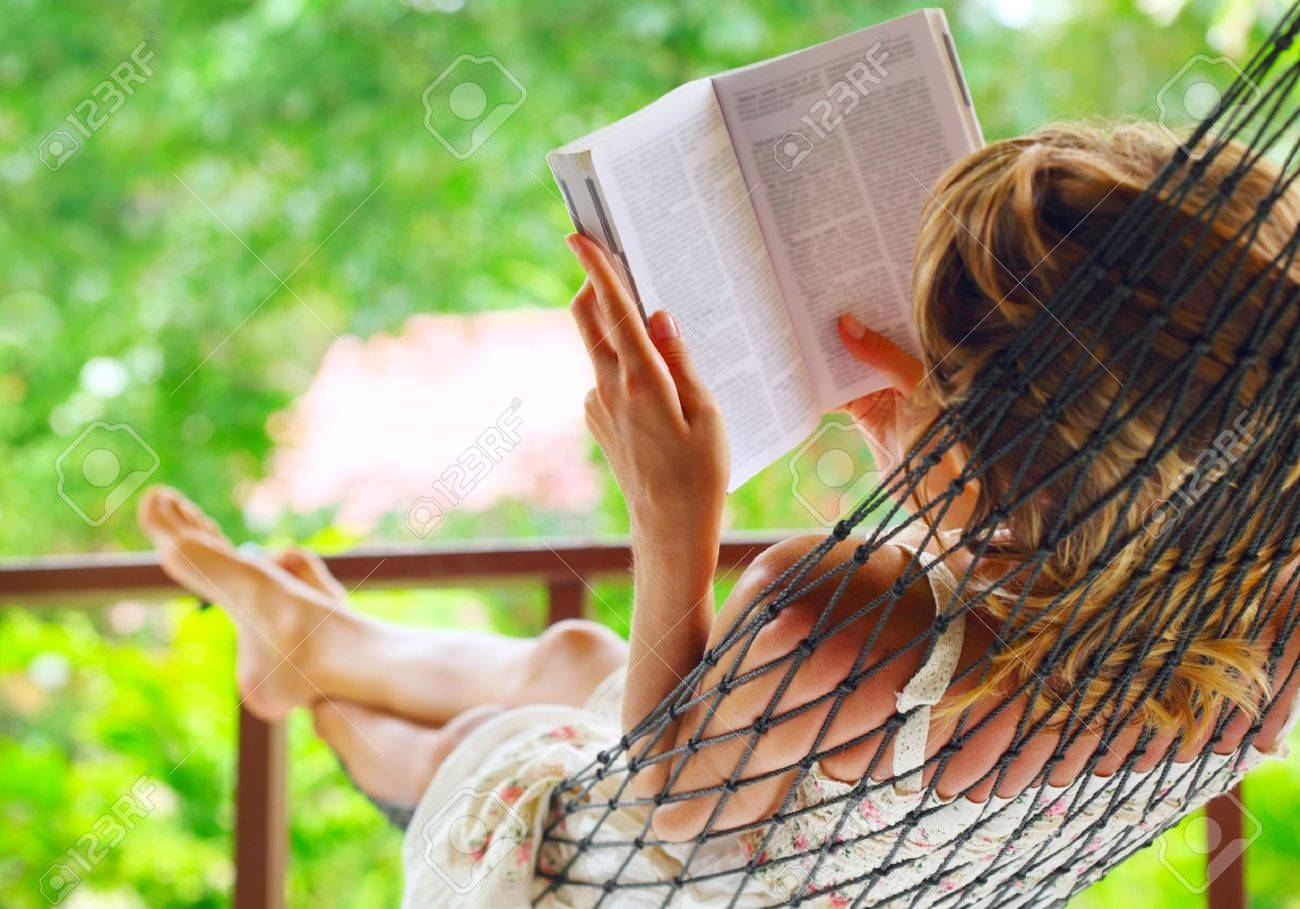 Young woman lying in hammock in a garden and reading a book. Shallow DOF. Focus on a left shoulder - 9912221