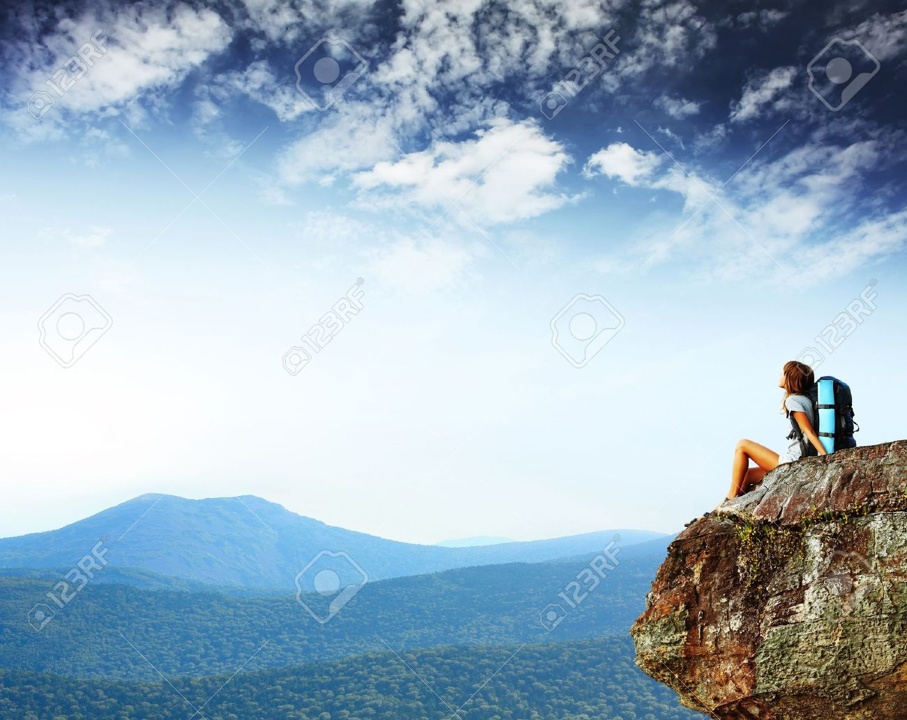 Young woman with backpack sitting on cliff's edge and looking to a sky - 11149604