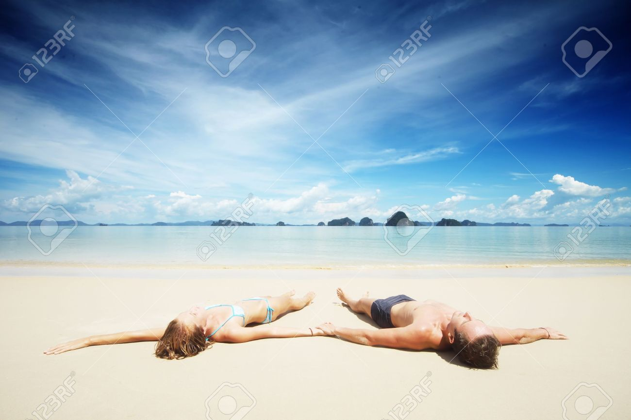 Young couple lying on a resort's white sand Stock Photo - 11540903