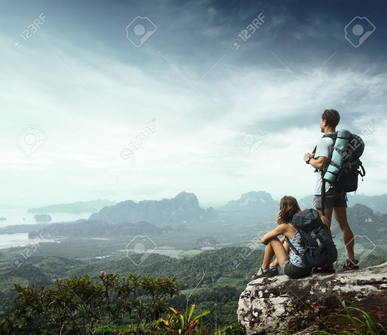 Young backpackers enjoying a valley view from top of a mountain Stock Photo - 16835806
