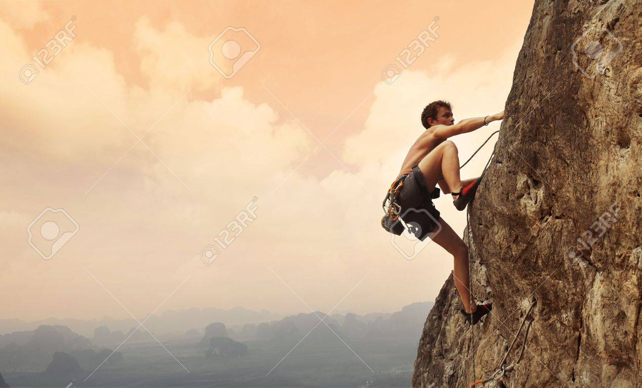Young man climbing on a limestone wall with wide valley on the background - 16835763