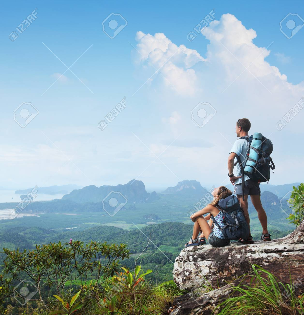 Young backpackers relaxing on top of a mountain and enjoying a valley view Stock Photo - 16840795