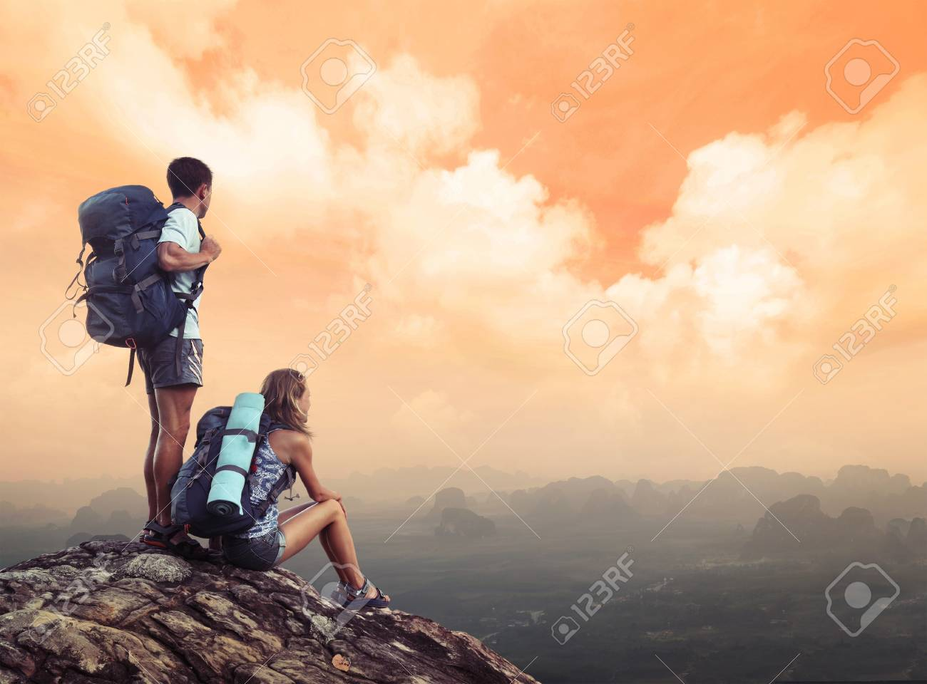 Two hikers with backpacks standing on top of a mountain and enjoying a valley view Stock Photo - 16840913