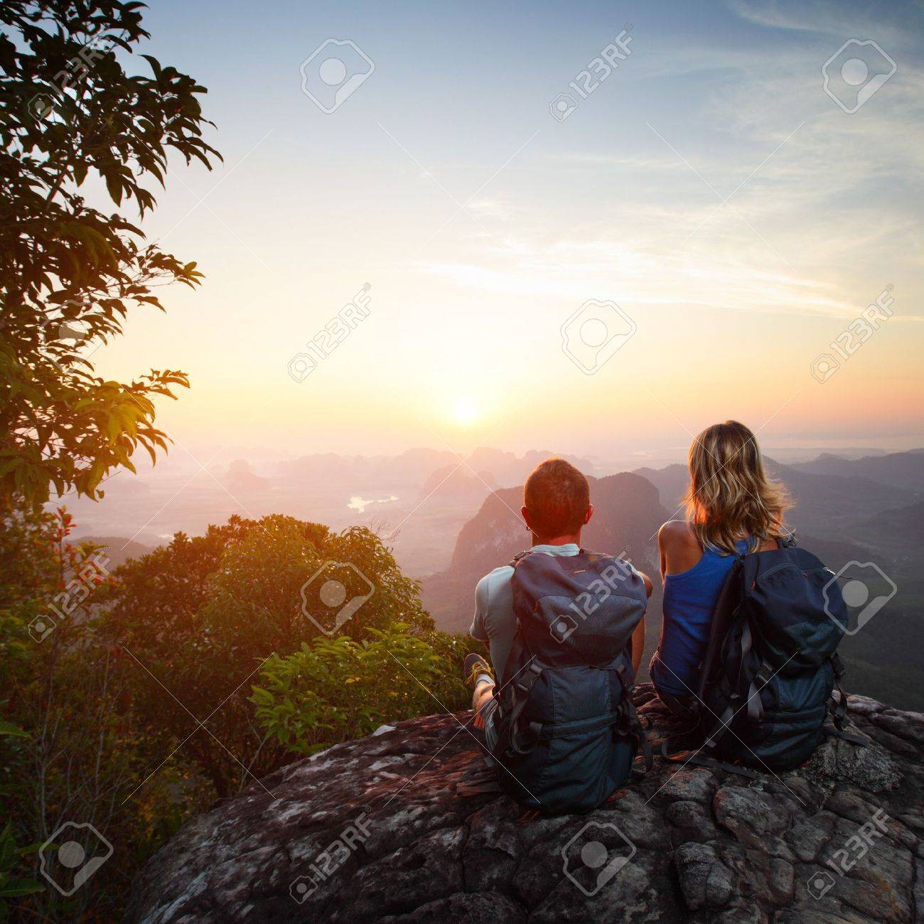 2a526e81ceb Stock Photo - Young couple with backpacks relaxing on top of a mountain and  enjoying valley view during sunrise