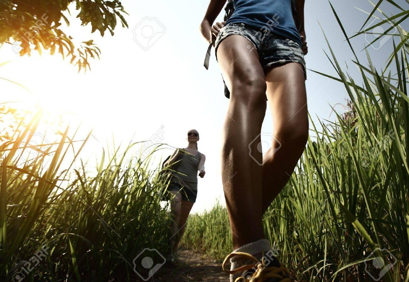 92d0c0fbff Standard-Bild - Zwei junge Damen mit Rucksäcken zu Fuß durch grünen  tropischen Wiese