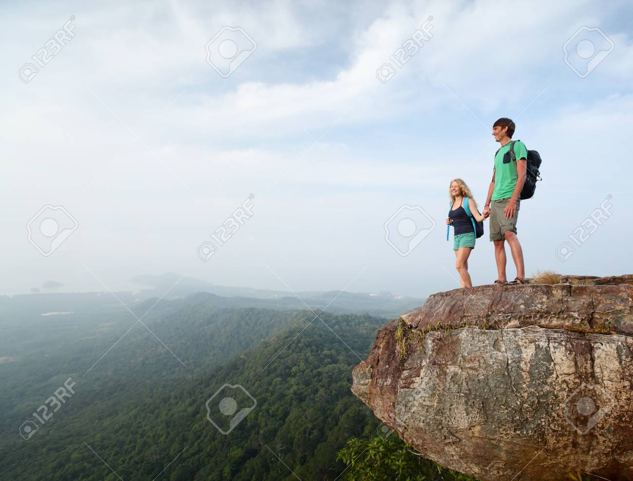Two hikers standing on top of a mountain and enjoying valley view Stock Photo - 19872754