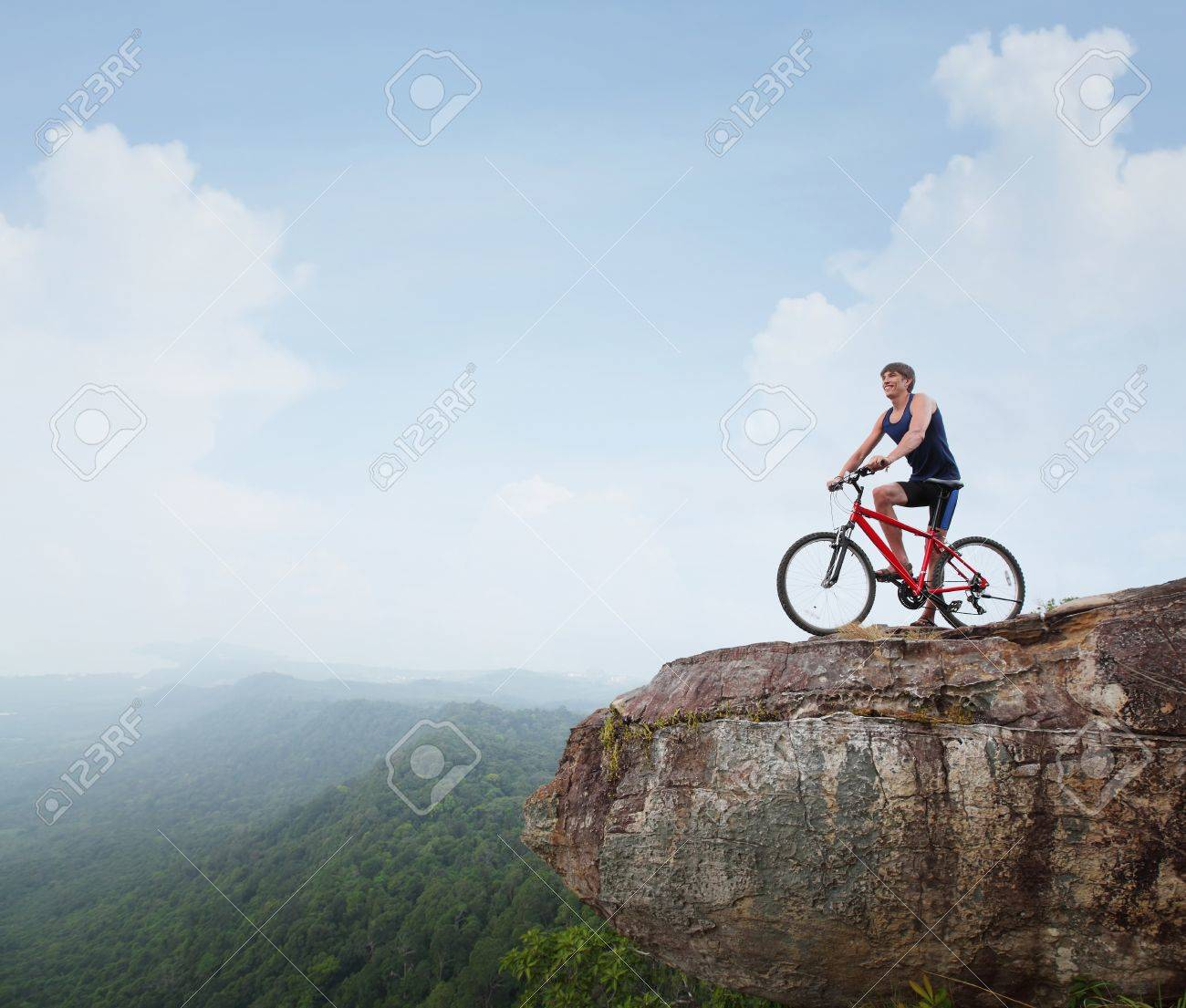 Young athlete standing on top of a mountain with bicycle and enjoying valley view Stock Photo - 19872871
